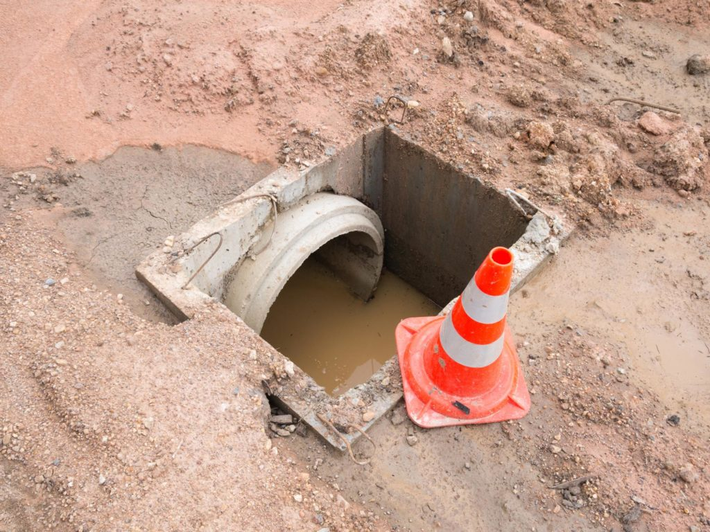 an open septic with orange cone sign
