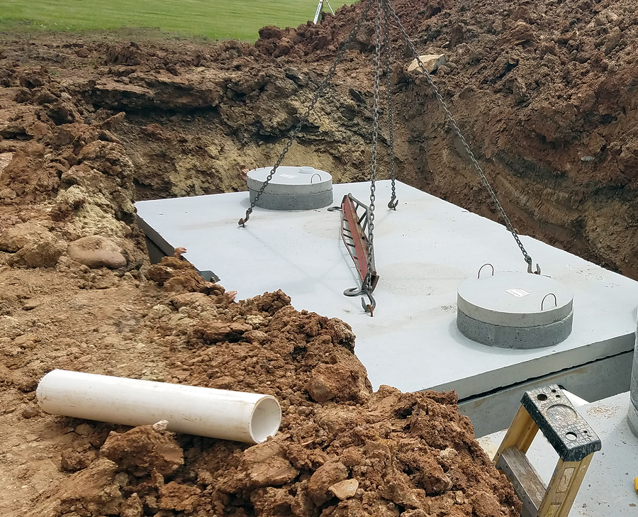 crane putting cement holding tanks in the ground for new home construction