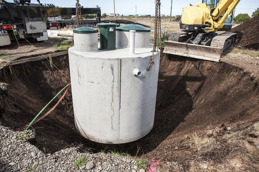 environmentally friendly septic tank being lowered into ground.